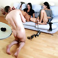 Two loose hoochies sitting on the couch tease their kneeled slave in the kinkiest manner imaginable.